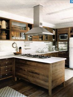 Modern kitchen with raw wood cabinets, white back splash, stainless steel faucets