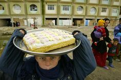 Un copil kurd vinde prăjituri de casă în apropierea unui stadion din oraşul Kirkuk, aflat la 255 de km nord de Bagdad, luni, 16 februarie 2004. Aproape 400 de familii refugiate sunt găzduite în interiorul stadionului. (  Daniel Mihailescu / AFP  ) - See more at: http://zoom.mediafax.ro/news/kurzii-10882572#sthash.sxNUolRN.dpuf