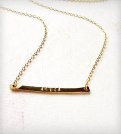 """A new twist on a custom stamped name necklace! One hand-forged 14K Gold Fill skinny banner is ready to be stamped with your name, nickname, monogram, sets of initials, etc. up to 11 letters. Numbers and """"&"""" character are also available. This piece hangs from 16"""" (40,6 cm) of 14k Gold Fill cable chain finished with a 14k Gold Fill clasp. Chain measures 16""""."""