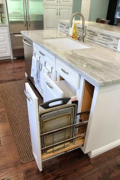 This kitchen has a gray marble top central island with easy pull out drawers for kitchen tools and essentials.