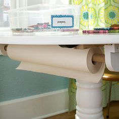 """""""Screw a holder for a spool of paper to the bottom of the table, and keep crayons and washable markers in plastic tubs nearby.  Editor's Tip: Turn the table over to mount the paper holder using wood glue and screws."""""""