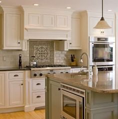 white cabinets with a light sage green subway tile as the backsplash. the main reason I saved this picture is for the microwave on the side of the island. what are your thoughts on the microwave placement. also the vent hood is made to look like a cabinet instead of a vent hood.
