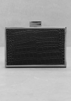 Edgy yet elegant, this rectangular box clutch features a slate-tone metal frame and embossed reptile-effect leather panels that give it a dark and mysterious vibe.