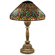 """Tiffany Studios 'Venetian' Desk Lamp, c. 1910 -- A Tiffany Studios leaded glass and bronze desk lamp comprising a """"Venetian"""" shade, featuring a richly colored pattern in blues, reds and greens, on gilt a bronze """"Venetian"""" desk base, the leading and bronze finish in a rich gold finish accented with green Tiffany Glass gems."""