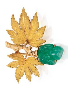 GOLD AND CARVED EMERALD CLIP-BROOCH, BUCCELLATI The textured gold branch suspending a carved emerald leaf measuring approximately 17.3 by 14.2 by 8.6 mm, gross weight approximately 10 dwts, signed Buccellati; late 1940s.