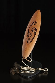 """Medium: tōtara, muka (New Zealand flax fibre), feathers (weka), MDF base. Size: 13 x x inches (on base). """"The piece is a contemporary take on a traditional instrument which is usually made of one piece of timber. I've used two seperate bits of tota Sculpture Art, Sculptures, New Zealand Flax, Flax Fiber, Polynesian Art, Wood Burning Tool, Maori Designs, Scale Art, Maori Art"""