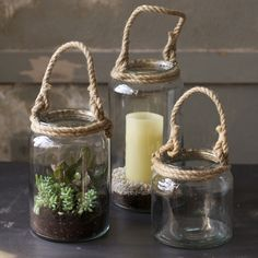 Recycled glass is used to shelter candles from the wind or create miniature, mobile gardens. Rope is twined around the top and knotted into handy handle. On Iron Accents.com
