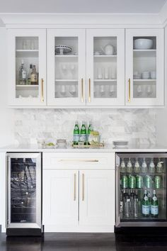 This white butlers pantry with shaker cabinets displays long brass pulls, under cabinet lighting and horizontal marble backsplash tiles.
