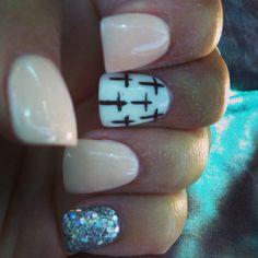 Nude and silver glitter nail design.
