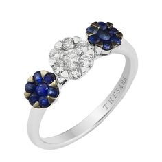 Three gemstone flowers are the focus of this 18k white and black gold ring. A 0.29 Carat T.W. diamond flower set in white gold and framed by two 0.38 Carat T.W. sapphire flowers set in black gold, offer a dramatic effect.