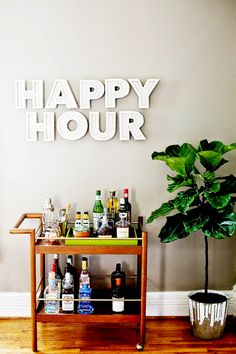 "Gold bar cart and indoor plant with marquee letters ""Happy Hour"""