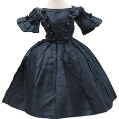 Of black silk taffeta, the two-piece gown features a fitted jacket with, dart-shaping, rounded neckline, black beads trim over long trumpet shaped