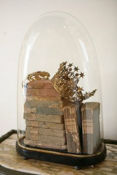 stacked books under glass topped by crowns