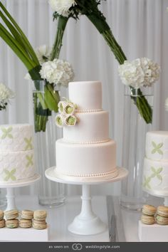 Three-tiered white fondant cake with floral appliqués.