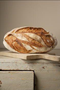 Farmhouse bread on wooden cupboard by Joerg Lehmann