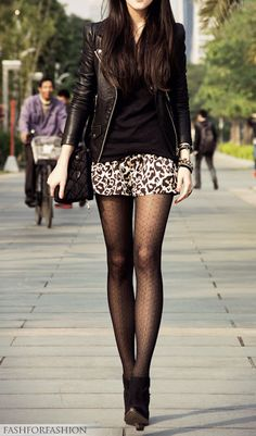 Black leather jacket, black top, printed shorts, black tights and booties