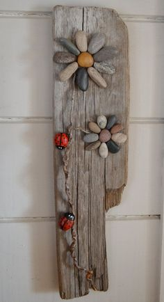 Lovely, unique piece of Great Lakes driftwood, adorned with hand gathered beach stones arranged into 2 flowers with twig stems on which crawl 2 hand painted ladybugs. A one of a kind piece, it would make a fantastic gift for that hard to buy for person on your list. Has a hook on the back for hanging and is signed and dated. Given a coat of varnish, BUT NOT SUITABLE for year round outdoor use in the elements. If you are able to give it a yearly coat of outdoor varnish it would stand up…