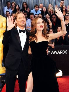 Best Actor nominee Brad Pitt and longtime love Angelina Jolie stay color-coordinated – and in sync! – while waving to fans at the Academy Awards.