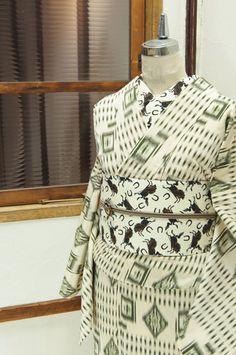 ベージュと黒の格子ラインパターンに、フォークロアムードただよう飾り模様がアクセントになった正絹御召の単着物です。