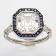 Art Deco Emerald/ascher cut diamond engagement ring   France   1930's   A stunning Emerald/Ascher cut 3.13 ct VS 1 F diamond is surrounded by sapphires and set in platinum. It comes with a GIA certificate. Listing via 1stdibs.