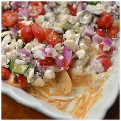 This festive Easy 7 Layer Greek Tzatziki Dip is layered with hummus, tzatziki sauce, cucumbers, tomatoes, black olives, red onions and feta cheese.