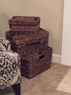 Pottery Barn baskets are hiding a power strip, modem, router, and cable box. A section of the middle basket was cut out so that it would work with the remote.