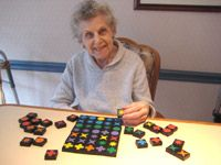 GAMES and ACTIVITIES for PERSON WITH DEMENTIA. The QwirkleTM game was chosen for Bernice partly because the wooden tiles are an easy size for her to handle, and because she loves colors and shapes. http://www.best-alzheimers-products.com/games-for-people-with-alzheimers.html