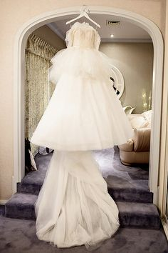 Fashionable wedding dress hanging at home.