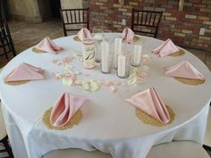 Romantic and simple centerpieces: candles with blush and ivory rose petals