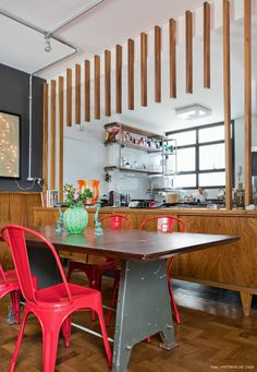 Cozinha integrada com sala de jantar com móveis de estilo industrial como a cadeira Tolix.
