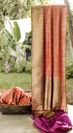 ALLURING PINK IRIDESCENT ORANGE BENARES SILK, WITH CLOSELY WOVEN PAISLEY MOTIS IN GOLD ALL OVER. THE MAGENTA WITH GOLD BORDER AND PALLU ADD TO THE MAJESTY OF THE PIECE