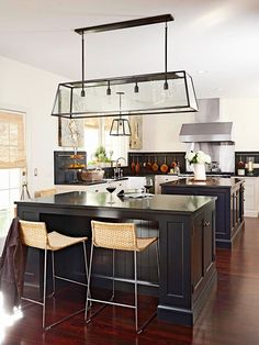 Light fixtures truly make a statement. A large oblong lantern fixture crowns the island, while a matching, smaller fixture hangs over the sink. Updated Kitchen, Diy Kitchen, Kitchen Dining, Kitchen Decor, Kitchen Ideas, Kitchen Layout, Kitchen Island, Dining Room, Dining Table