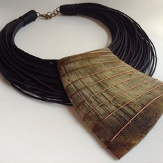 Necklace by Patrícia Moura Biojoias. Lord knows what this thing is -- maybe copper-wire-wrapped horn on cord -- but damn it's impresssive