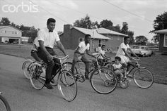 Cassius Clay, soon to be known as Muhammad Ali, bicycles near his parents' house in Louisville, Kentucky. (1963) © Steve Schapiro/Corbis