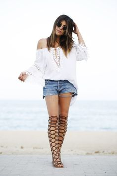 How to Wear High Gladiator Sandals this Summer   Street Style Outfit Inspiration   'Dulceida' in white off-the-shoulder blouse, cutoff denim shorts, and brown knee-high gladiator sandals