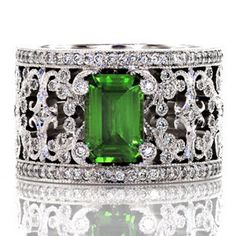 Britty - Intricate pierced scrolls created in 14k white gold and adorned with bead set diamonds. The Britty design showcases the emerald cut green gem stone with distinction by four diamond capped prongs. Two rails of shared prong round diamonds are finished with hand applied milgrain on our Knox Signature heirloom band.