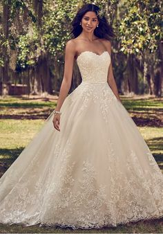 Lace motifs cascade over tulle in this ballgown wedding dress, featuring a strapless scoop neckline and belt with bow detail. Finished with covered buttons over zipper and inner corset closure.