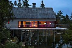 A house on stilts sits over a lush New England landscape.