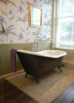 Nice pebbled rock highlights the claw-foot bathtub and looks great next to the wood.