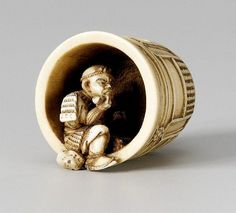 An ivory netsuke of Benkei. Second half 19th century. Depicted smoking a twisted pipe and taking a rest inside the bell of Miidera, which he has single-handedly carried up Mount Hiei, so that the sound of the bell could be enjoyed by the monks of the mountain temples.