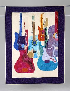 GUITAR QUILT art quilt by Mariann Crowley. The quilt is embellished with guitar pics, yarns, buttons and crystals