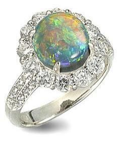 A black opal and diamond ring.  Set with an oval black opal, within a surround of round brilliant-cut diamonds, between diamond-set shoulders, mounted in platinum, the opal estimated to weigh approximately 2.70 carats, the diamonds estimated to weigh approximately 1.20 carats in total, ring size 5¾. Via Bonhams.