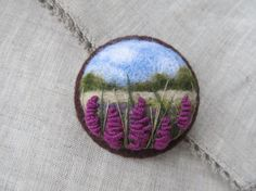 Needle felted brooch with a landscape,decorated with embroidery.Brooch is fitted with a metal brooch pin.  5.5cm in diameter