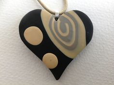 "Code:  13-87  A modern heart shaped polymer clay pendant.   The pendant is handmade by Margaret Young. It measures approx 2"" across  and has a drop of just over 2"" It features a lovely soft beige swirl and spot design on a black ground. Has a sterling silver bail and sterling silver end fastenings. Is strung on a lovely neutral coloured 18"" cord. Co-ordinating earrings and cufflinks available."