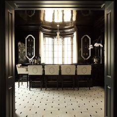 Hollywood regency bar features glossy black lacquered walls fitted with niches filled with glass shelves housing libations flanking bay window dressed in black and white curtains.