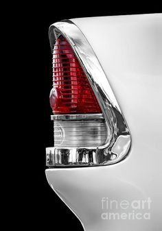 A detailed view of the rear tail light section of a classic white 1955 Chevrolet.