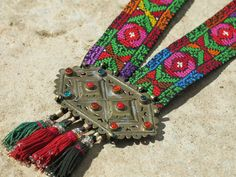 Kinship Stories: Ethnic necklace whose base comes from a vintage Palestinian cross-stitched belt. The bronze centerpiece is Turkoman and comes from Afghanistan. The tassels are vintage Uzbek. They come from old tapestry. This necklace is entirely handmade and is a unique piece.