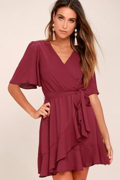 We have fallen hard for the Absolute Affection Burgundy Wrap Dress! Lightweight fabric falls from fluttering short sleeves into a surplice bodice. Elasticized waist, with sash belt, tops a flirty, ruffled wrap skirt.
