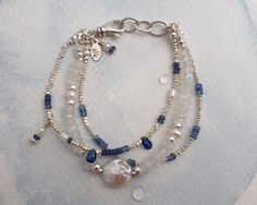 Moonstone, Sapphire, Kyanite, Pearl, and Sterling Silver bracelet. Sterling Silver lobster clasp with extra links fits a 6 1/2 to 7 inch wrist. Let me know if you need a smaller or larger size! Although my bracelets may be similar they are never exactly alike, so your bracelet will be unique.    ***    Moonstones are probably one of the most mystical of gemstones and filled with meaning. It is said that moonstones bring good fortune, can help to foretell the future, enhance intuition, bring…