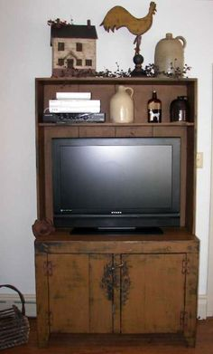 primitive flat screen tv cabinet, mustard color and worn . Lots of storage in bottom cabinets. www.primitivepassions-onlinefurniture.com 609 420-4460